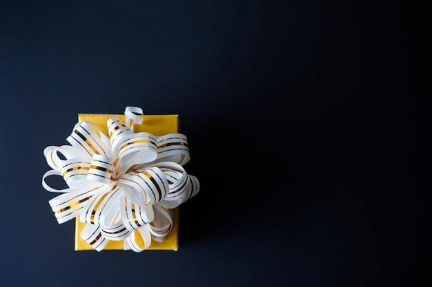 Elegante confezione regalo avvolto in nastro a strisce bianche e oro su sfondo nero con texture. Foto Premium