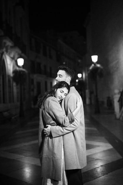Elegante donna attraente che abbraccia con il giovane sulla strada di notte Foto Gratuite