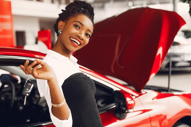 Elegante donna nera in un salone di auto Foto Gratuite