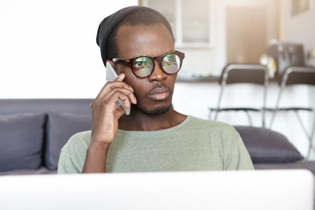 Elegante giovane afroamericano con gli occhiali e cappello seduto sul divano nella hall dell'hotel con il computer portatile e avendo una conversazione seria sul cellulare. persone, stile di vita e tecnologia Foto Gratuite
