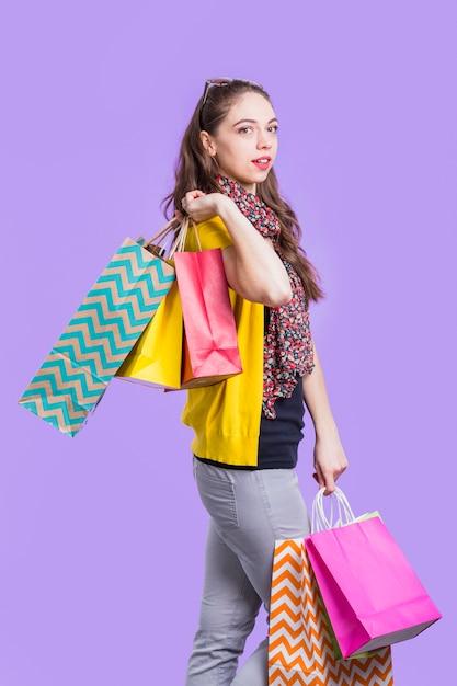 Elegante giovane donna che porta il sacchetto di carta colorata Foto Gratuite