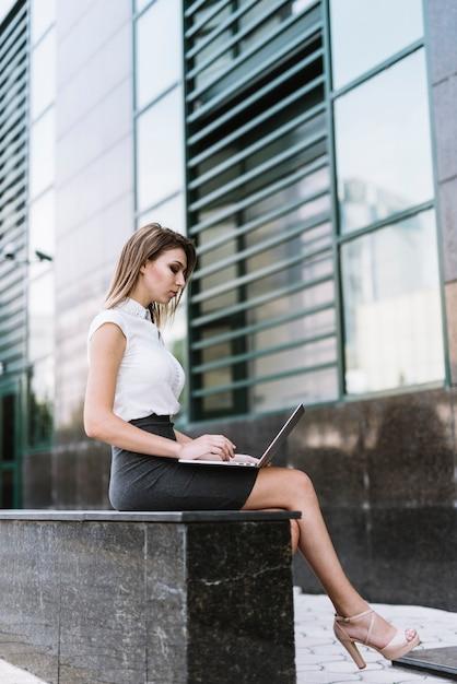 Elegante giovane imprenditrice seduto sulla panchina utilizzando il portatile a all'aperto Foto Gratuite