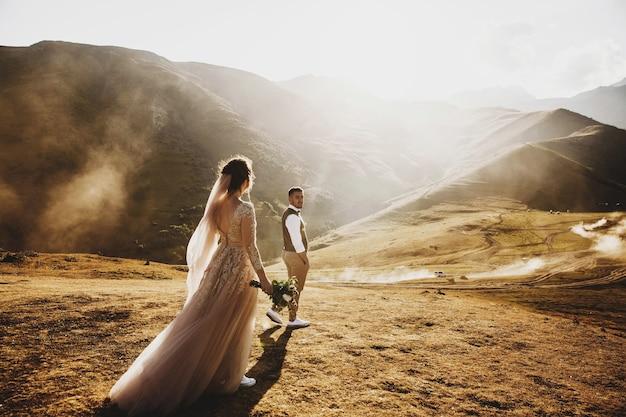 Elegante giovane sposi si diverte in posa nelle splendide montagne georgiane Foto Premium