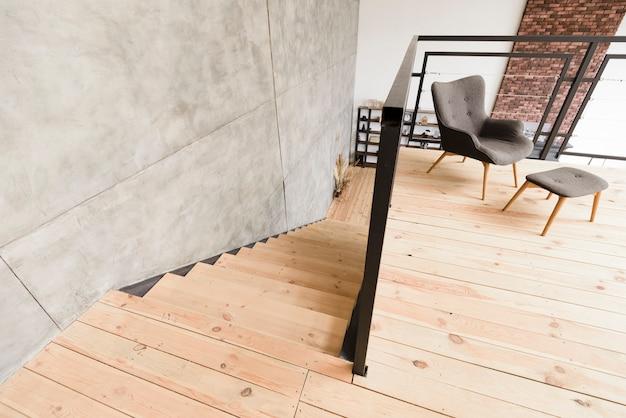 Elegante poltrona moderna e sgabello vicino scala Foto Gratuite