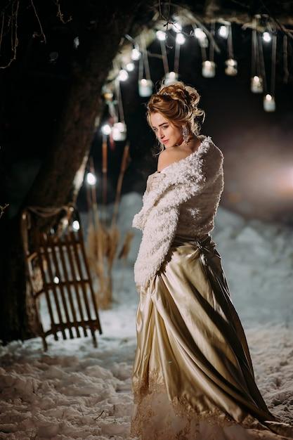 Elegante ragazza millenaria una sera d'inverno con luci Foto Premium