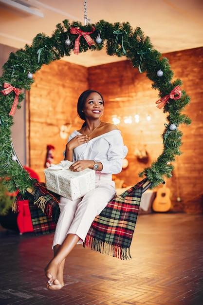 Elegante ragazza nera nelle decorazioni natalizie Foto Gratuite