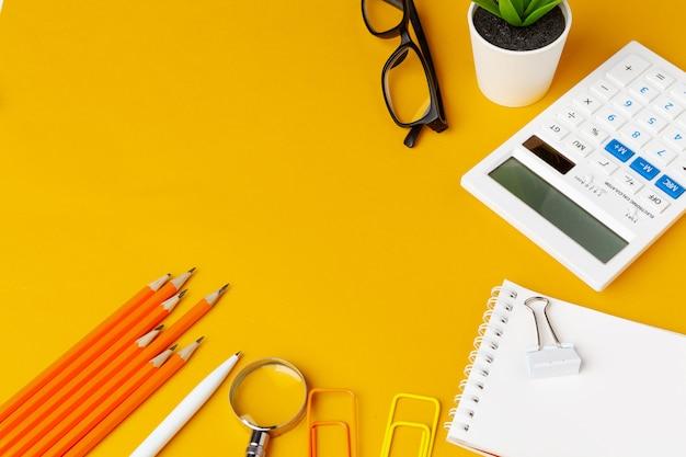 Elegante scrivania gialla disordinata con vista dall'alto di vari articoli di cancelleria Foto Premium