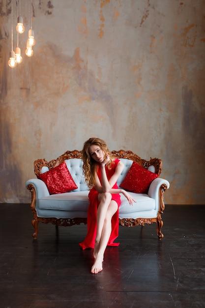 Elegante sensuale giovane redhair donna in abito rosso seduto sul divano classico Foto Gratuite