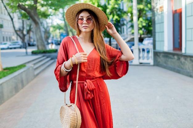 Elegante splendida signora in abito lungo corallo a piedi all'aperto. colori estivi vivaci. look da strada alla moda. Foto Gratuite