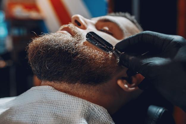 Elegante uomo seduto in un negozio di barbiere Foto Gratuite