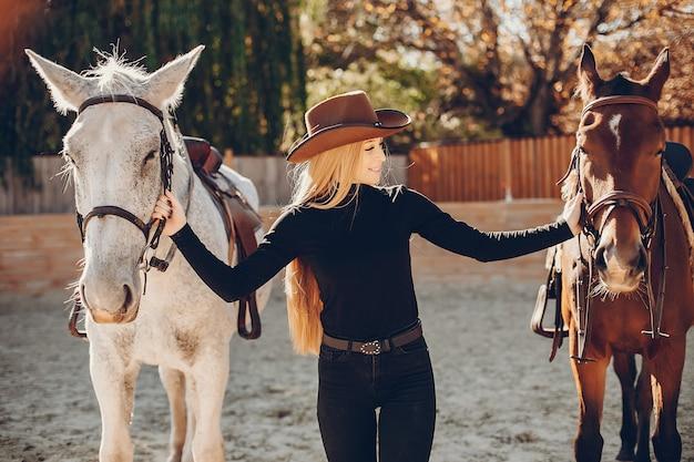Elegants ragazza con un cavallo in un ranch Foto Gratuite