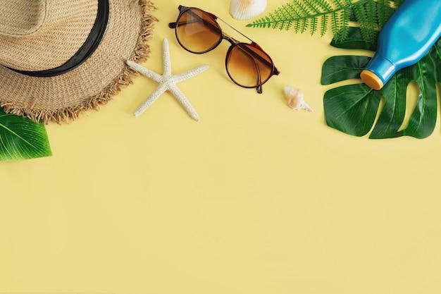 Elementi degli accessori di viaggio su fondo giallo, concetto di vacanze estive Foto Premium