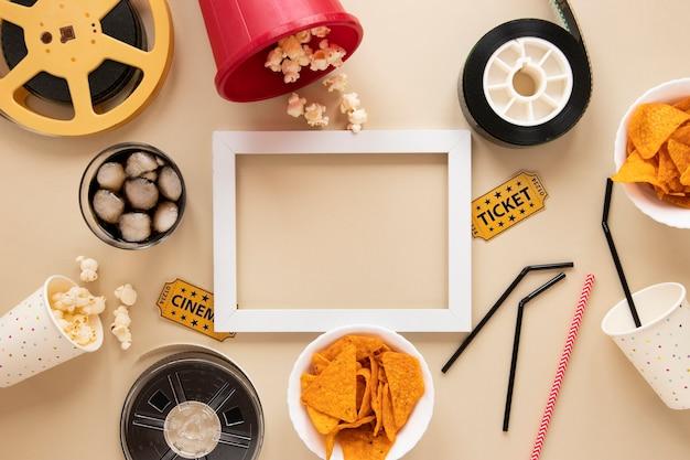 Elementi del cinema su sfondo beige con cornice vuota bianca Foto Gratuite