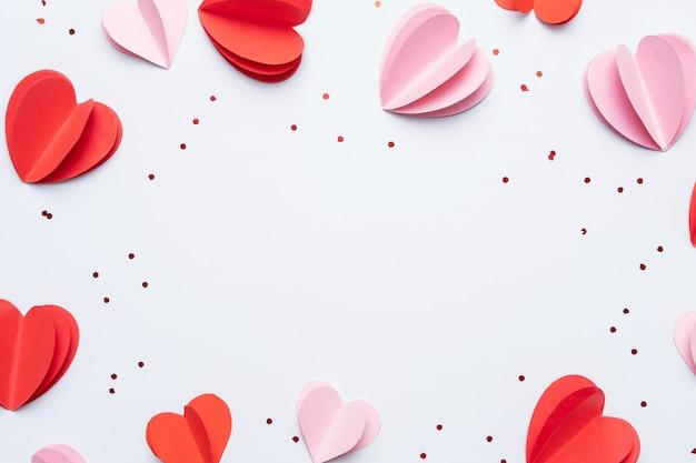 Elementi di carta a forma di cuore su sfondo bianco. simboli d'amore per happy women, mother's, san valentino, compleanno. vista dall'alto del biglietto di auguri. disteso Foto Premium
