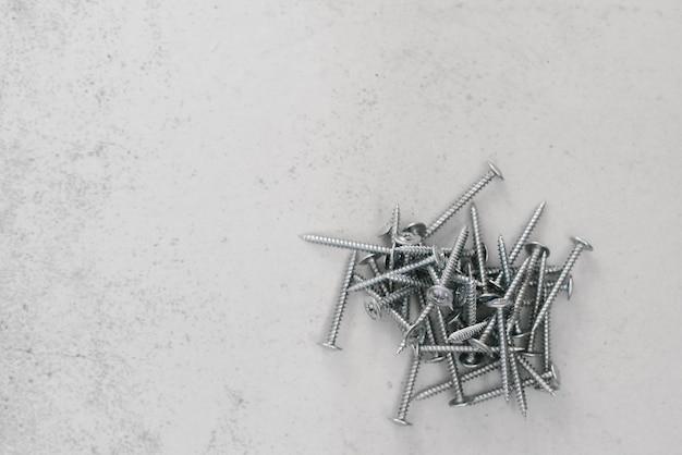 Elementi di fissaggio per l'edilizia, viti su uno sfondo grigio chiaro. copia spazio Foto Premium