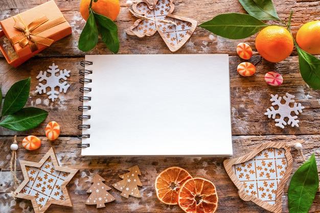 Elenco vuoto di desideri e cornice da decorazioni natalizie e mandarino Foto Premium