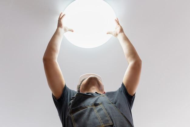 Elettricista con il casco bianco che controlla illuminazione al soffitto nella casa, concetto del tecnico. Foto Premium