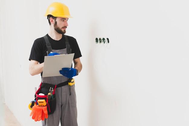 Elettricista con tavoletta di carta guardando i buchi Foto Gratuite