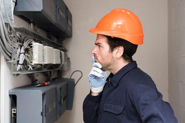 Elettricista maschio che esamina circuito e pensiero Foto Gratuite
