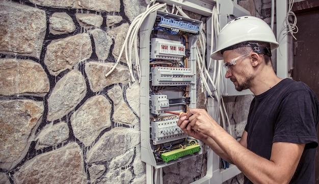 Elettricista maschio lavora in un quadro con una cabina di collegamento elettrica Foto Gratuite