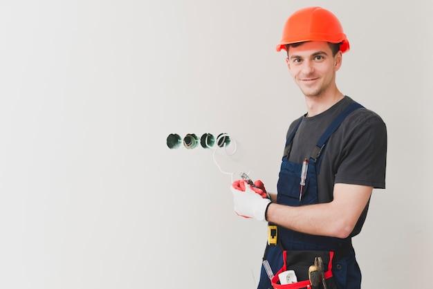 Elettricista sorridente ai fori di ostruzione Foto Gratuite