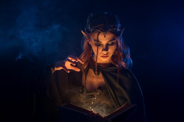 Elfo dai capelli rossi in diadema d'argento che impara gli incantesimi dal libro. Foto Premium