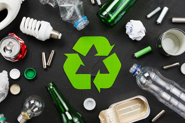 Emblema di riciclaggio intorno a rifiuti su sfondo nero Foto Gratuite