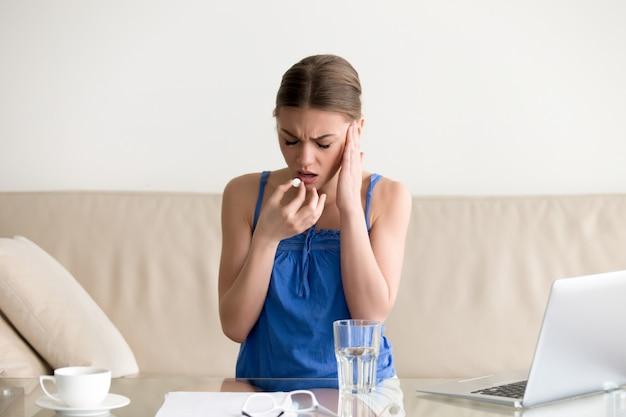 Emicrania della sensibilità della donna e pillola bevente a casa Foto Gratuite