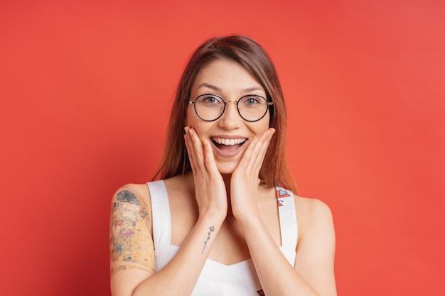 Emozioni della gente - ritratto della ragazza positiva sorpresa sopra la parete rossa Foto Gratuite