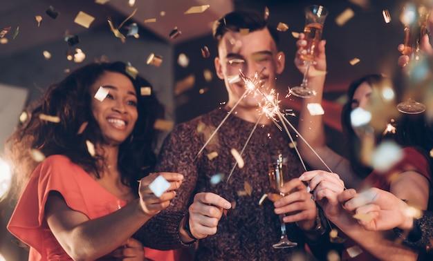 Emozioni sincere amici multirazziali festeggiano il nuovo anno e tengono in braccio luci e bicchieri di bengala Foto Premium
