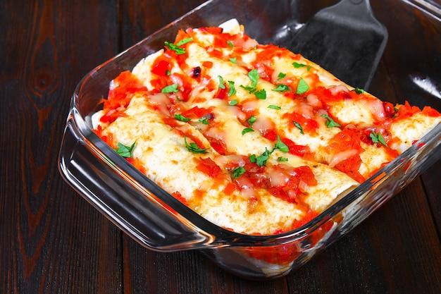 Enchiladas di pollo fatto in casa in piatto sulla tavola di legno. vista dall'alto. Foto Premium
