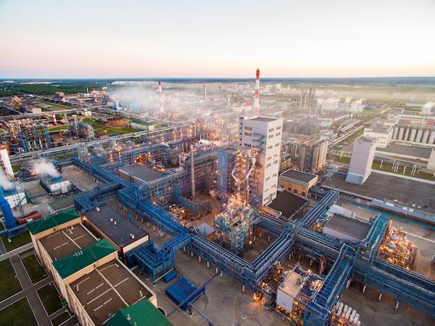 Enorme raffineria di petrolio con strutture metalliche, tubi e distillazione del complesso con luci accese al crepuscolo. vista aerea Foto Premium