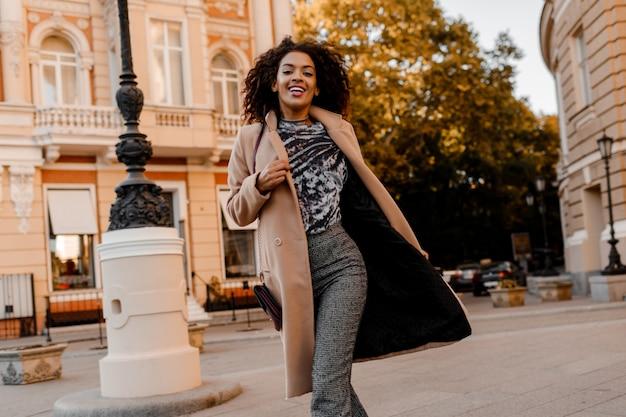 Entusiasta donna africana in elegante abito casual correre e divertirsi. Foto Gratuite