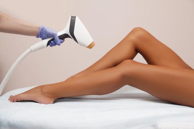 Epilazione laser e cosmetologia nel salone di bellezza. procedura di depilazione epilazione laser, cosmetologia, spa e concetto di epilazione. bella donna che ottiene rimozione dei capelli sulle gambe Foto Premium