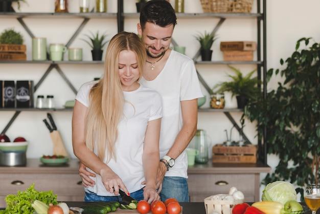 Equipaggi abbracciare la sua amica che taglia le verdure sul contatore di cucina Foto Gratuite