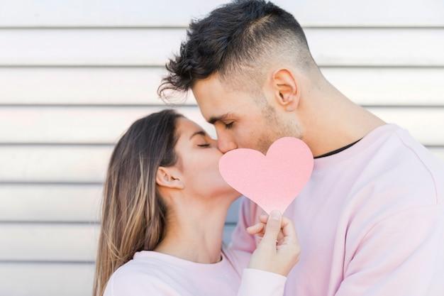 Equipaggi baciare la donna che tiene il cuore di carta decorativo Foto Gratuite