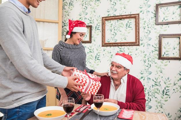 Equipaggi dare il contenitore di regalo all'uomo anziano in cappello rosso di santa Foto Gratuite