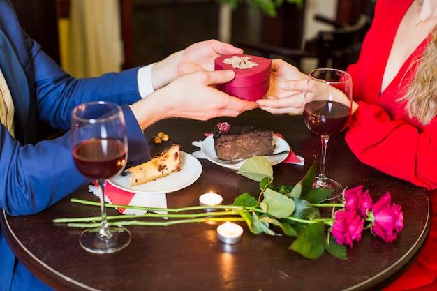 Equipaggi dare il piccolo contenitore di regalo alla donna alla tavola in ristorante Foto Gratuite