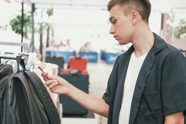 Equipaggi i sacchetti della spesa della tenuta che scelgono lo zaino che esamina l'etichetta del prezzo da pagare al negozio del deposito Foto Premium