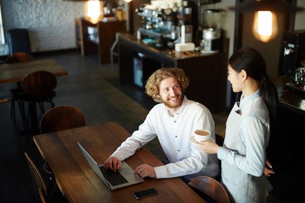 Equipaggi il caffè bevente al ristorante mentre lavorano al computer portatile Foto Gratuite
