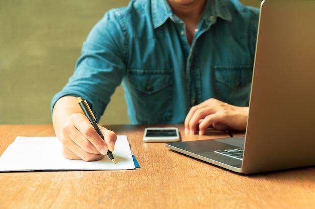 Equipaggi il documento di scrittura su lavoro di ufficio con il computer portatile ed il telefono cellulare sullo scrittorio di legno Foto Premium