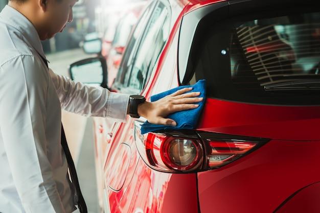 Equipaggi il faro asiatico dell'ispezione e l'autolavaggio dell'attrezzatura per la pulizia con l'automobile rossa per la pulizia alla qualità al cliente sull'automobile showroom di servizio di trasporto automobilistico del trasporto dell'automobile. Foto Premium