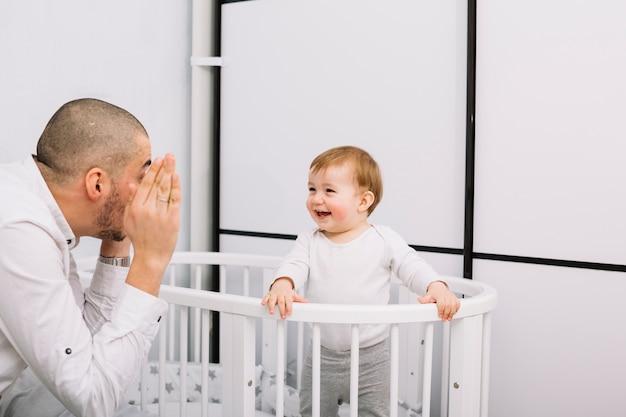 Equipaggi il gioco con il piccolo bambino sorridente in greppia Foto Gratuite