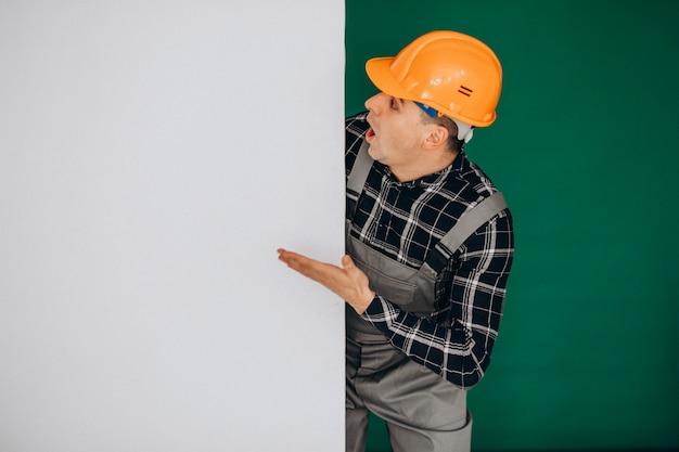 Equipaggi il lavoratore in casco isolato sulla parete verde Foto Gratuite