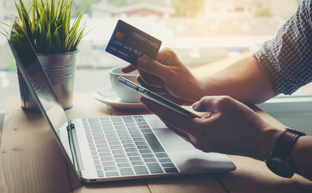 Equipaggi il pagamento con carta di credito della tenuta che compera online sullo smart phone Foto Premium