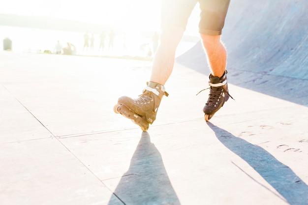 Equipaggi il pattinaggio a rotelle nel parco del pattino durante il giorno soleggiato Foto Gratuite