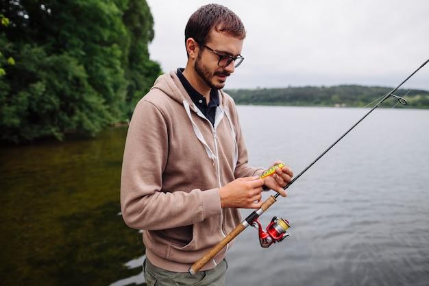 Equipaggi il richiamo della tenuta e la canna da pesca vicino al lago Foto Gratuite