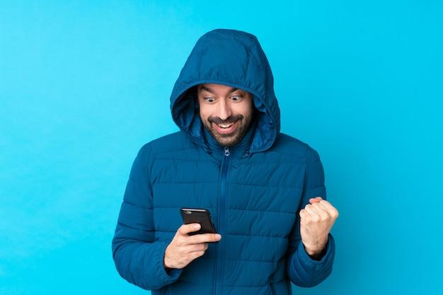 Equipaggi il rivestimento invernale da portare e la tenuta del caffè asportabile sopra la parete blu isolata sorpresa e l'invio del messaggio Foto Premium