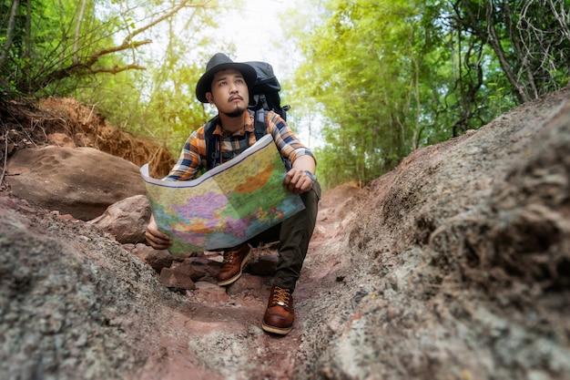 Equipaggi il viaggiatore con la mappa di seduta e della lettura dello zaino nella foresta Foto Premium
