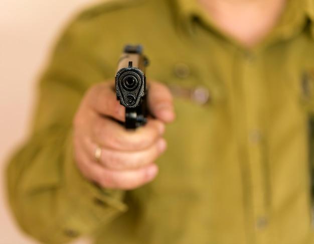 Equipaggi indicare la pistola all'obiettivo con una mano Foto Premium